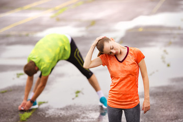 Couple stretching in rainy weather