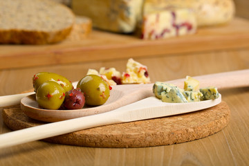 Olives and cheese on a wooden spoons