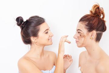 two women applying exfoliating