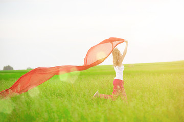 Young lady runing with tissue in green field. Woman with scarf.