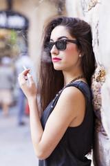 Glamorous brunette woman with sunglasses smoking, retro style.