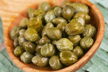capers in a wooden spoon