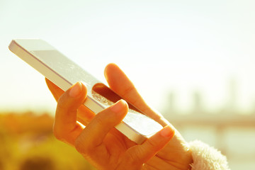 Women hand holding a smart phone with sunrise background