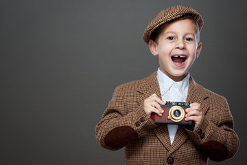 Cute boy with old photo camera.