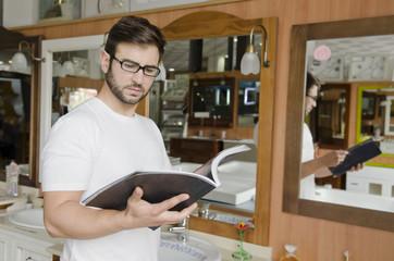Man looking catalog at bath store