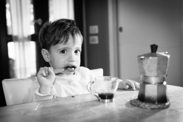 Cute toddler drinking italian coffee made with moka
