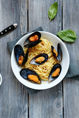 Pasta topped with mussels and basil