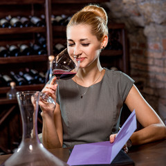 Woman tasting wine in the cellar