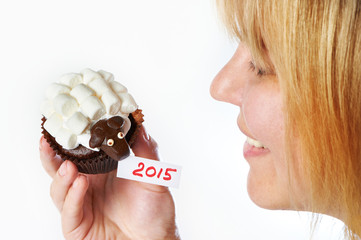 Young woman holds cake lamb as simbol 2015 new years isolated