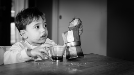 Cute toddler drinking italian coffee made with moka