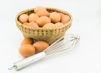 eggs in basket and hand whisk on white background