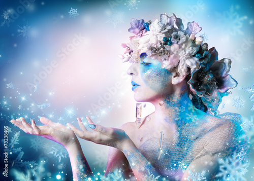 canvas print picture Winter portrait of woman blowing snowflakes