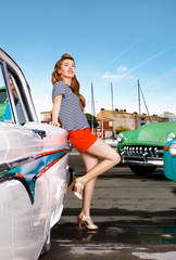 Girl in pin-up on a background of retro cars. port