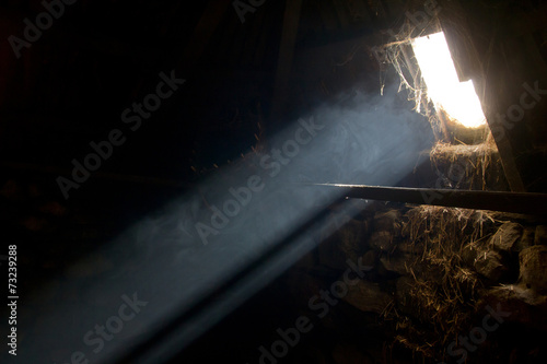 A bright sunbeam enters an old hay barn - 73239288