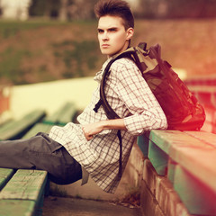 Fashion lifestyle portrait of handsome hipster man with backpack