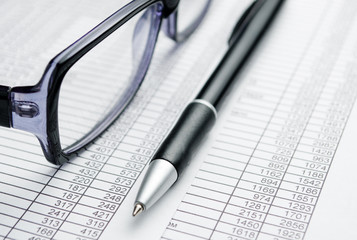 Eyeglasses and Pen on Top of Report Papers