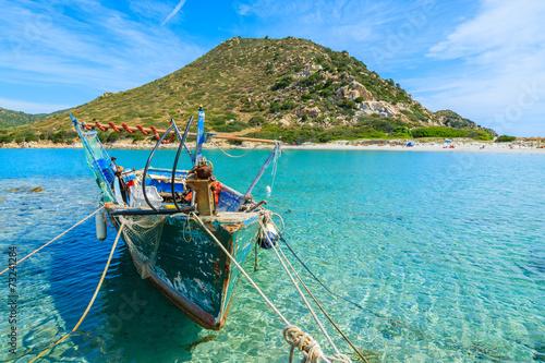 Fishing boat on sea water at Punta Molentis bay, Sardinia island - 73241284