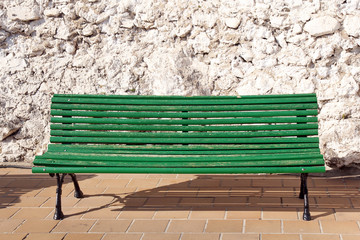 green wooden bench against ancient stone wall