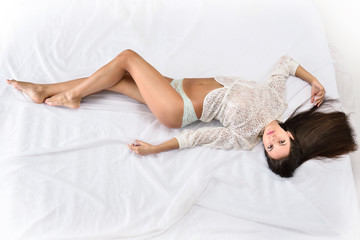 beautiful seminude woman with long hair on the white bed