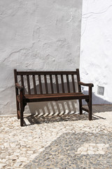vintage wooden bench against whitewashed wall