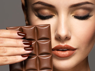 Beautiful woman with brown nails holds bar of chocolate