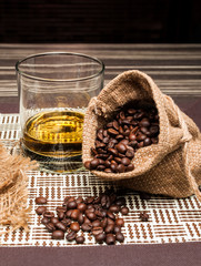 coffee beans and whiskey on a wooden background