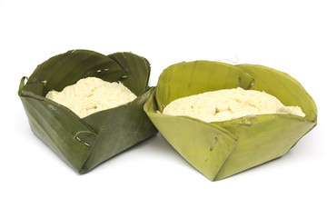Egg custard wrapped in a banana leaf on a white background.