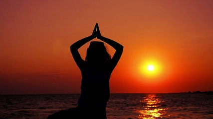 Silhouette of a girl at sunset yoga pose