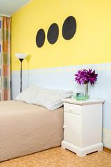 Кровать с тумбочкой. Декоративные цветы. Голубые и желтые обои.