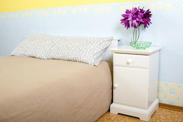 Кровать с тумбочкой. Декоративные цветы. Голубые и желтые обои