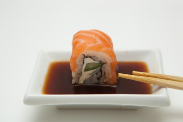 Piece of philadelphia roll in the soy sauce