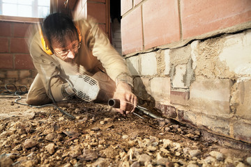 Builder working with chipping hammer