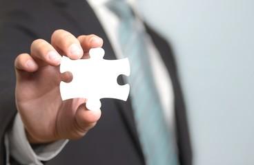 Businessmann hält Puzzleteil