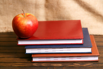 Notebooks and apple on wooden table over grunge background