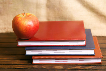 Notebooks and apple on wooden table