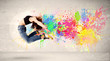 Leinwanddruck Bild - Happy teenager jumping with colorful ink splatter on urban backg