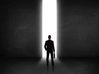 Business person looking at wall with light tunnel opening