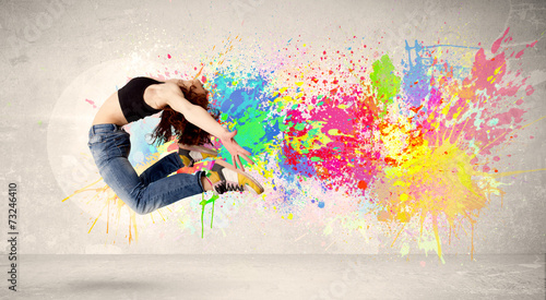 Leinwanddruck Bild Happy teenager jumping with colorful ink splatter on urban backg
