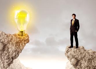 Businessman on rock mountain with idea bulb