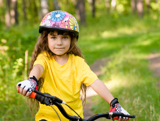 little girl on bike looking at camera and smiling