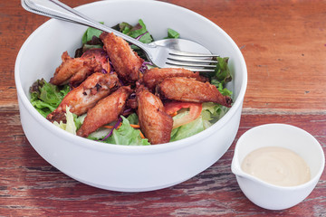 Dressing salad with fried chicken wing in white bowl