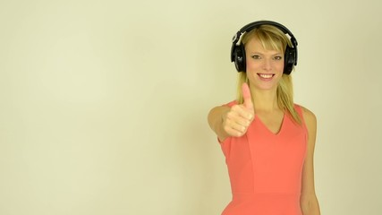 woman listens to music with headphones and shows a thumb up to