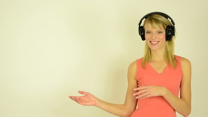 woman listens to music headphones-woman presents (introduce)
