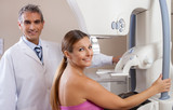 Young woman in 30s undergoing scan at mammography machine with h poster