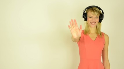 woman listens to music with headphones and waves goodbey