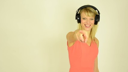 woman listens to music with headphones and woman pointing