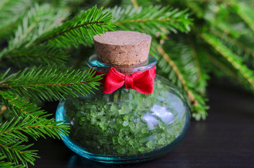 Small bottle of bath salt and christmas tree branches