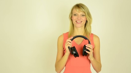 woman listens music with headphones - woman takes off headphone
