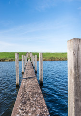 Concrete jetty and wooden poles in water