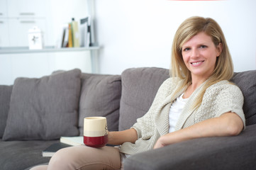 woman standing on sofa with cup of..